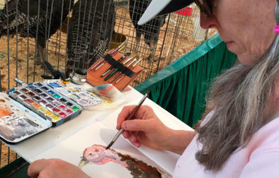 "My friend Terri Wentzka took this photo of me as I sketched a turkey at the Fair, using my portable ""table."" The entire table is attached to a monopod. The brush holder is in the top right corner of the table."